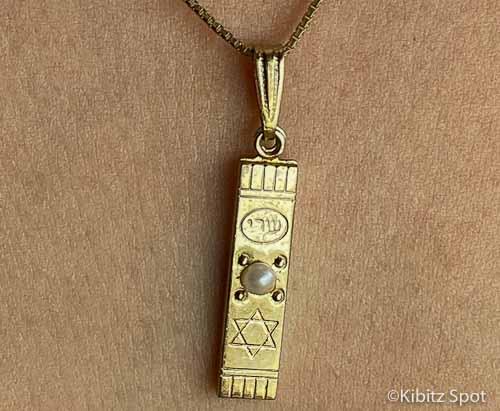 Mezuzah pendant on a gold chain.