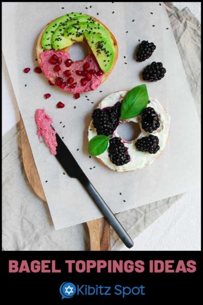 An open faced bagel with cream cheese, berry, avocado, and pomegranate toppings