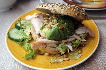Turkey with avocado and pine nuts sandwich made on a bagel