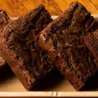 Four homemade brownies on a plate made from the ultimate gooey chocolate brownie recipe