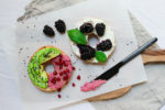Pomegranate, avocado, and berries on separate a bagel