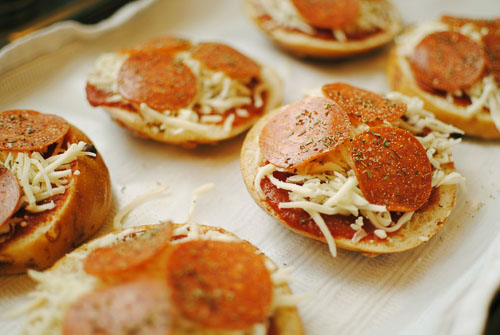 Pizza bagel topped with sauce, cheese, and salami