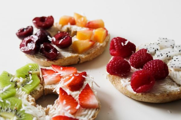 Bagels smeared with cream cheese and topped with different fruits and shredded coconut
