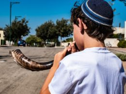 Boy blowing a shofar, a rams horn trumpet used in Jewish ceremonies