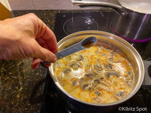 Adding fish sauce to our nearly completed tom kha gai soup recipe