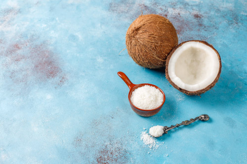 an open coconut and a measure of shredded coconut for the best coconut pie recipe