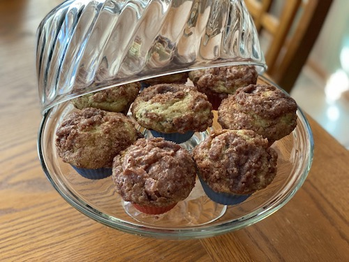 Cinnamon Zuccini Muffins on a glass cake plate with lid