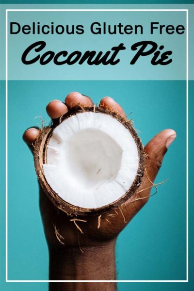 Half a coconut held in a hand with the white flesh of the coconut seen