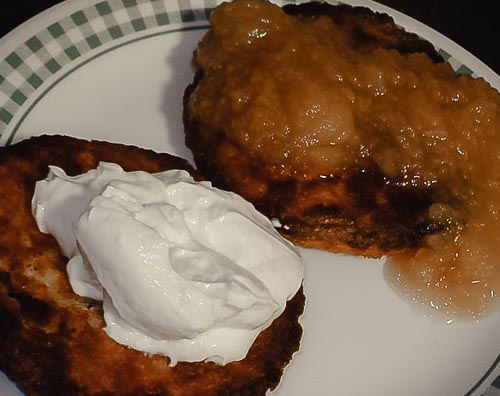 Two latkes on a plate, one topped with applesauce, the other with sour cream