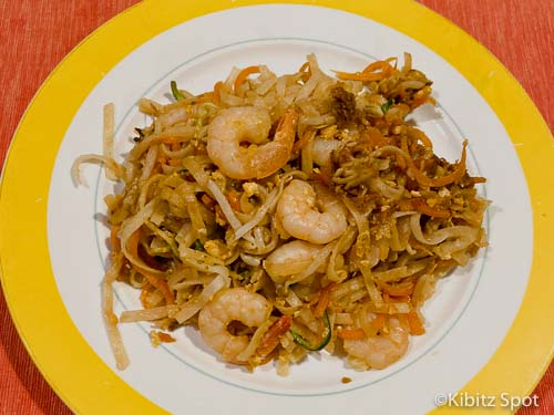 A plate of healthy pad thai featuring shrimp, vegetables, and rice noodles.