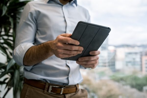 man holding tablet, photo from waist to neck