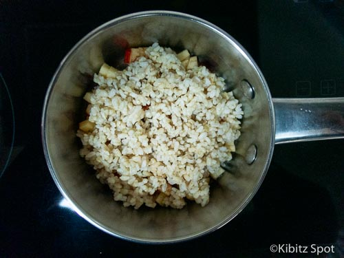 Rice added on top of apple and cinnamon in a pot