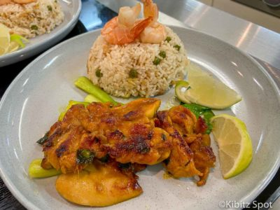 One serving of Vietnamese grilled chicken with rice, green vegetables and lime wedges
