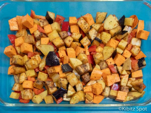 kumara, potato, eggplant, spices, and olive oil diced for egg casserole in an oven safe dish