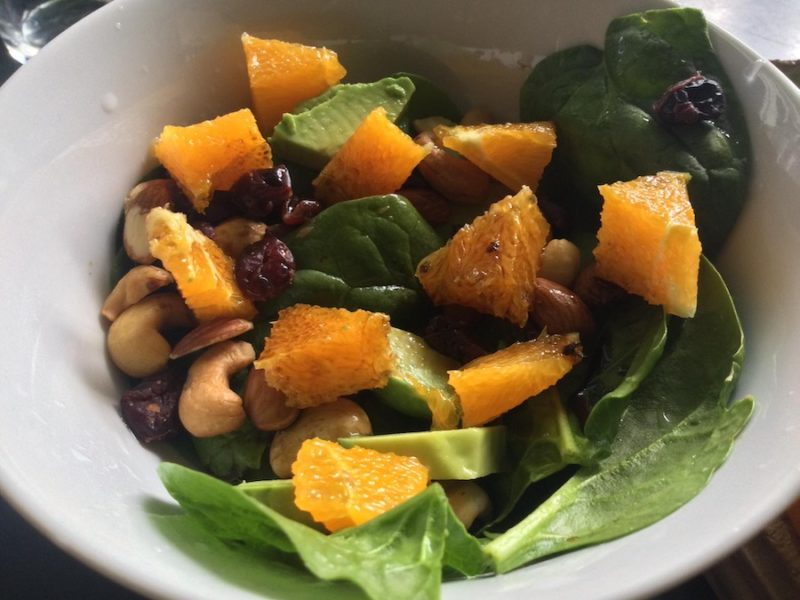 Finished salad with grapefruit, spinach, avocado, nuts, dried fruit, and balsamic vinegar