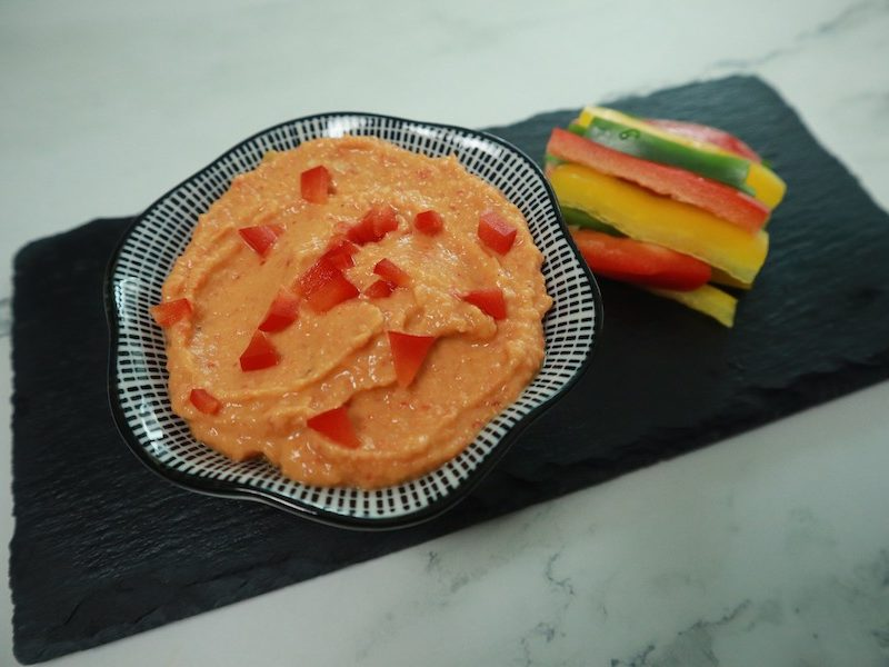 red pepper hummus recipe prepared with veggie sticks for dipping