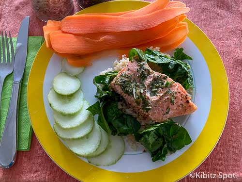 baked Salmon and Spinach served over rice with a side of carrots and cucumber on a plate